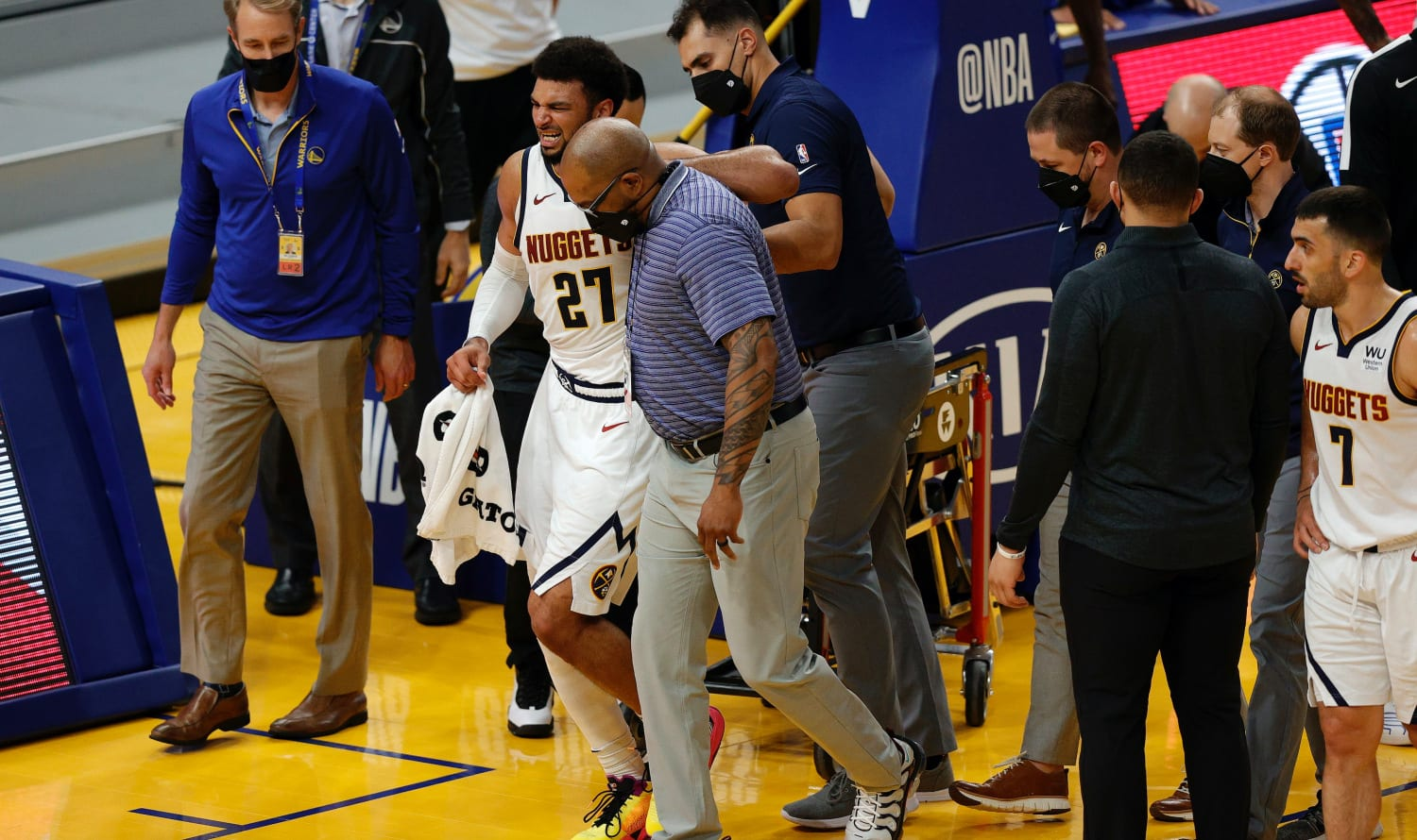 Nuggets star Jamal Murray being helped off the court